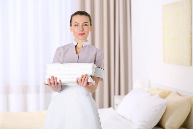 Attraktives zimmermädchen, das einen haufen sauberer handtücher im zimmer hält