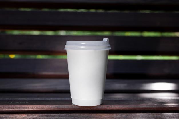 Attrappe, lehrmodell, simulation. weißbuchkaffeetasse mit schwarzem deckel auf der bank