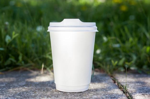 Attrappe, lehrmodell, simulation. weißbuchkaffeetasse mit schwarzem deckel im grünen gras