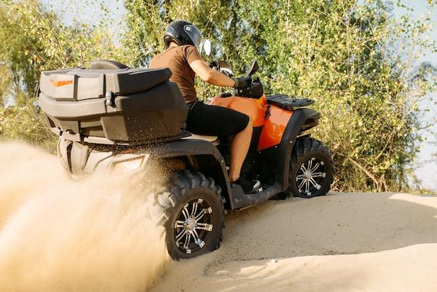 Atv-reiten in aktion, sandsteinbruch im hintergrund, extremsport. männlicher fahrer im helm auf quad im sandkasten