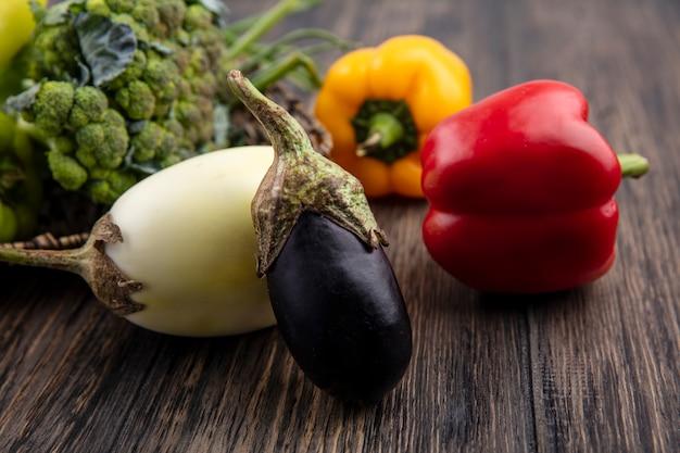 Aubergine der seitenansicht mit farbigem paprikabrokkoli und frühlingszwiebeln auf hölzernem hintergrund