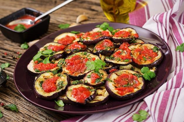 Aubergine gegrillt mit tomatensauce, knoblauch, koriander und minze. veganes essen. gegrillte aubergine.