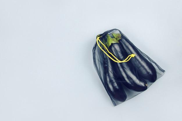 Aubergine in einer schwarzen einkaufstüte auf einem grauen hintergrund