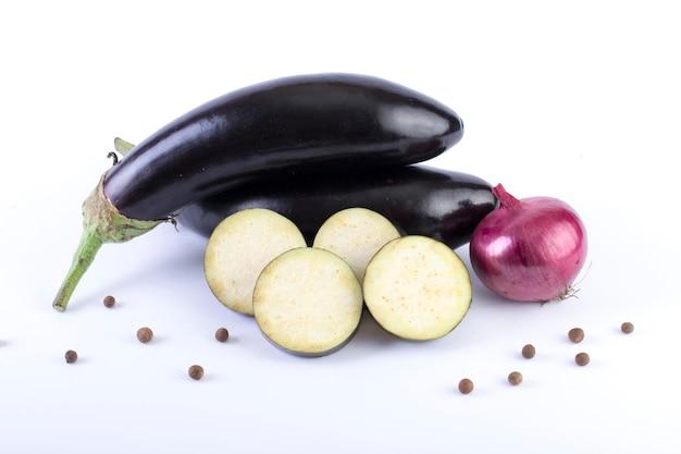 Aubergine mit roter zwiebel auf weißem hintergrund. auberginen sind frisch und lecker. frisches gemüse auf weißem grund.