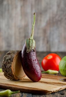 Aubergine mit zitrone, tomate, paprika, holzseitenansicht auf holz und schneidebrett