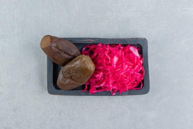Aubergine und eingelegter rotkohl auf dem brett