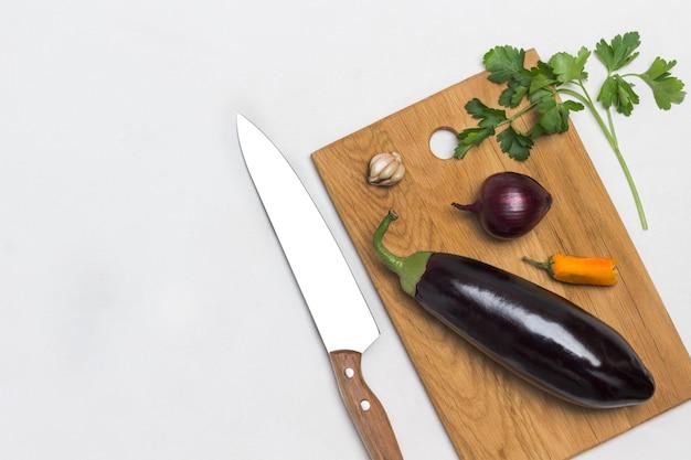 Aubergine und zwiebel auf schneidebrett zweig petersilie und küchenmesser auf tisch
