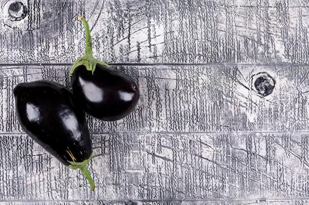 Auberginen auf grauem holz. draufsicht. freier speicherplatz für ihren text
