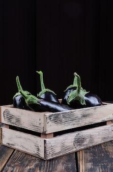 Auberginen der seitenansicht in der holzkiste auf hölzernem und schwarzem hintergrund. vertikaler raum für text