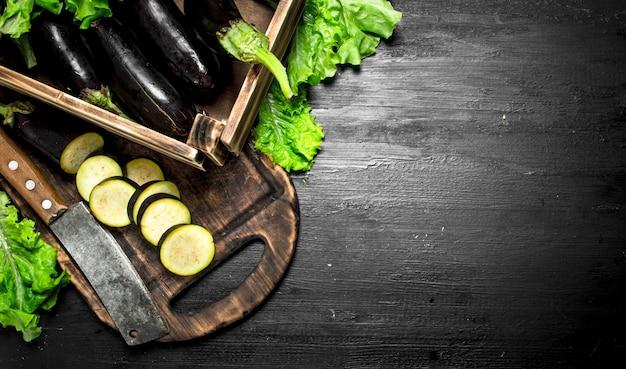 Auberginen in einer alten schachtel mit gehackten scheiben an der schwarzen tafel