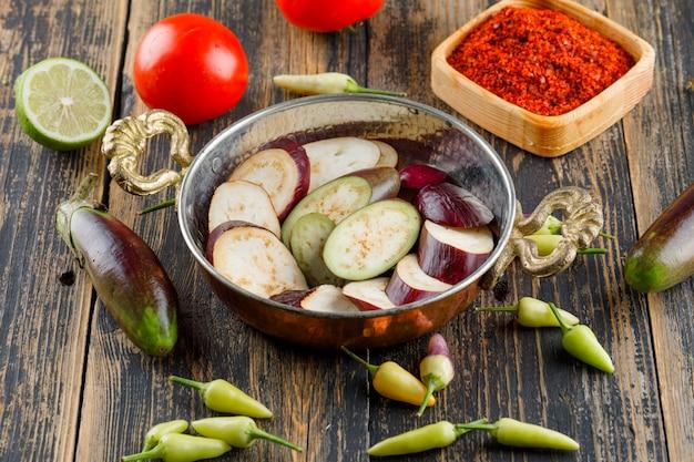 Auberginen mit gewürzen, paprika, tomaten, limette in einer pfanne auf holz, blickwinkel.