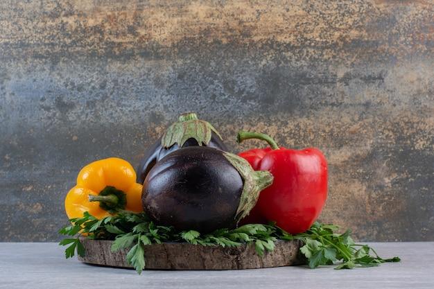 Auberginen, paprika und petersilie auf holzstück. hochwertiges foto