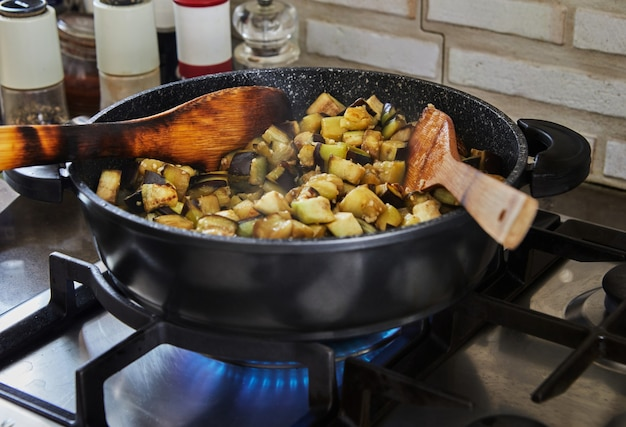 Auberginen werden in der küche nach rezept aus dem internet in der pfanne auf dem gasherd gebraten.