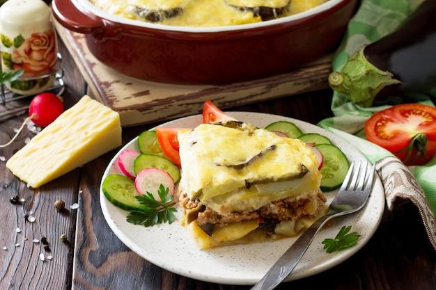 Auberginenauflauf mit beshamel moussaka auf dem küchenholzhintergrund