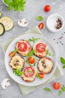 Auberginenpizza mit tomatensauce, mozzarella-pilzen und frischem basilikum vegetarisches gericht