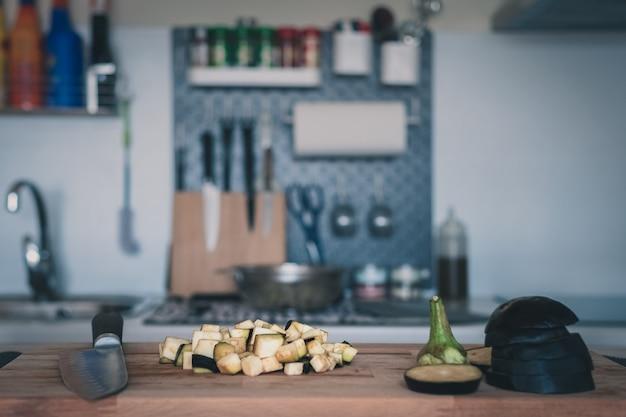 Auberginenwürfel auf einem schneidebrett und einer modernen unscharfen küche