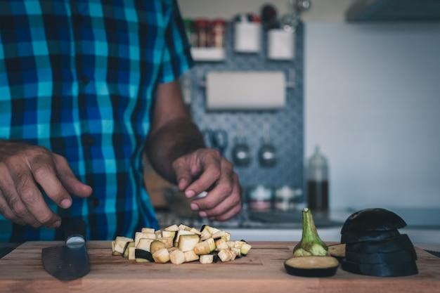 Auberginenwürfel auf schneidebrett und einem mann, der mit einer flockigen modernen küche erscheint