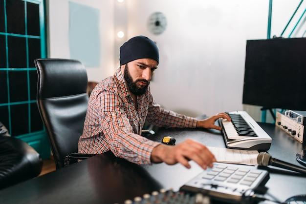 Audio engineering, mann arbeiten mit musikalischer tastatur im studio. professionelle digitale tonaufnahmetechnologie