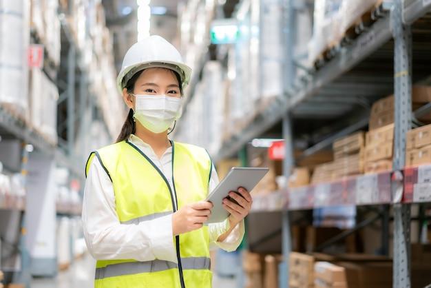 Auditorin oder auszubildende der jungen frau trägt eine maske, die während der covid-pandemie im lager arbeitet
