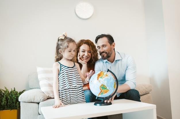 Auf abenteuer gehen, mama, papa und tochter studieren globus.