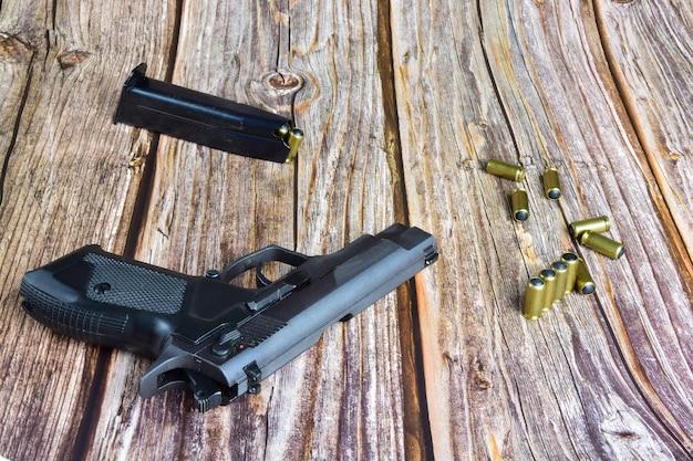 Auf alten braunen holzbrettern liegen eine schwarze pistole und mehrere traumatische patronen.