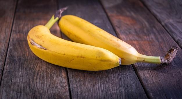 Auf alten holzbohlen liegen zwei köstliche reife bananen mit rissigen schalen