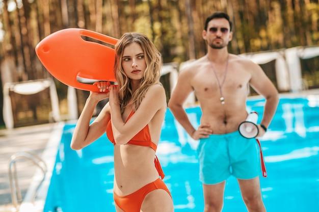 Auf arbeit. zwei bademeister laufen in der nähe des öffentlichen schwimmbads und unterhalten sich