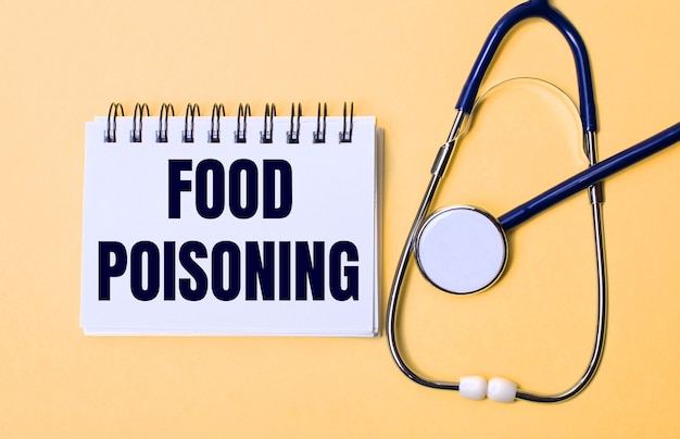 Auf beigem hintergrund ein stethoskop und ein weißer notizblock mit der aufschrift food poisoning
