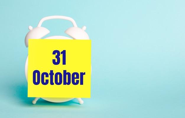 Auf blauem hintergrund - ein weißer wecker mit einem gelben aufkleber für notizen mit dem text 31. oktober