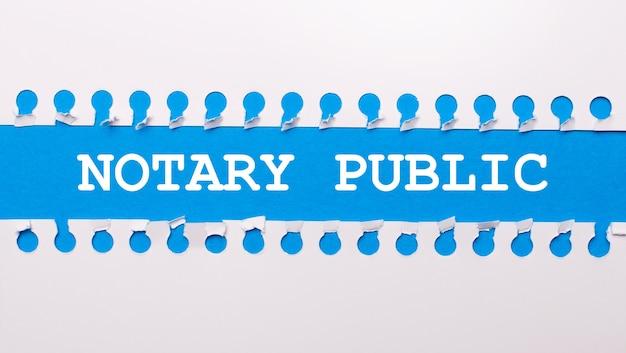 Auf blauem hintergrund mit text notary public zwei weiße zerrissene papierstreifen.