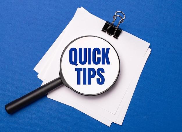 Auf blauem hintergrund weiße blätter unter einer schwarzen büroklammer und darauf eine lupe mit dem text quick tips
