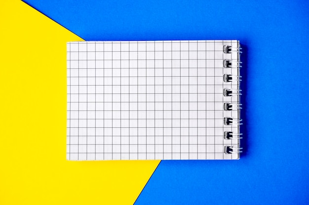 Auf blauem und gelbem grund liegt ein rundes notizbuch mit in einem käfig aufgereihten seiten. vorlage für ihren text. notizblock aus leerem papier auf hellem zweifarbigem hintergrund für ihr design, draufsicht