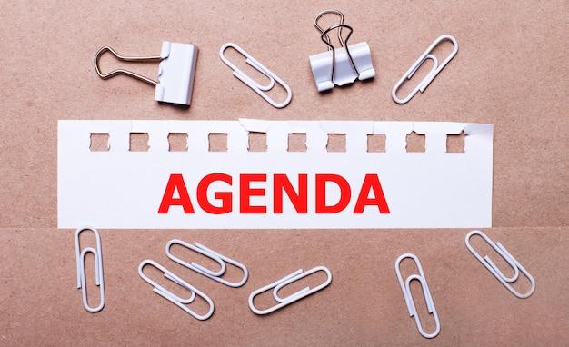 Auf braunem hintergrund weiße büroklammern und ein abgerissener weißer papierstreifen mit dem text agenda