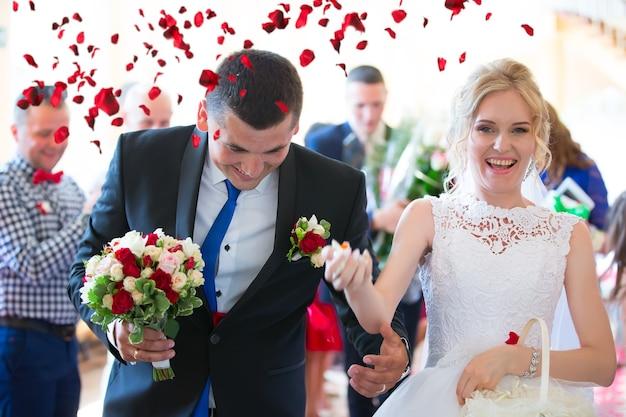 Auf das brautpaar werfen sie rosenblätter. braut und bräutigam glücklich in rosenblättern