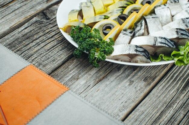 Auf dem alten holztisch schön auf dem teller ist eine makrele und ein hering dekoriert