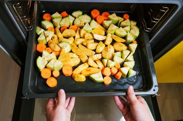 Auf dem backblech sind geschnittene zucchini, karotten und kartoffeln. hände halten backblech.