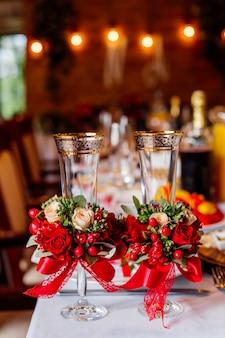 Auf dem banketttisch stehen zwei leere hochzeitsgläser, geschmückt mit viel grün, roten rosen und einem band