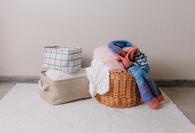 Auf dem boden liegen dinge, die zum waschen in einem weidenkorb vorbereitet sind. ordnung und reinigung des hauses