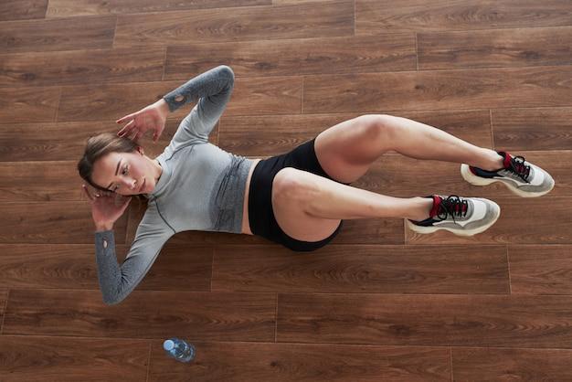Auf dem boden üben. sportliche junge frau haben fitness-tag im fitnessstudio zur morgenzeit