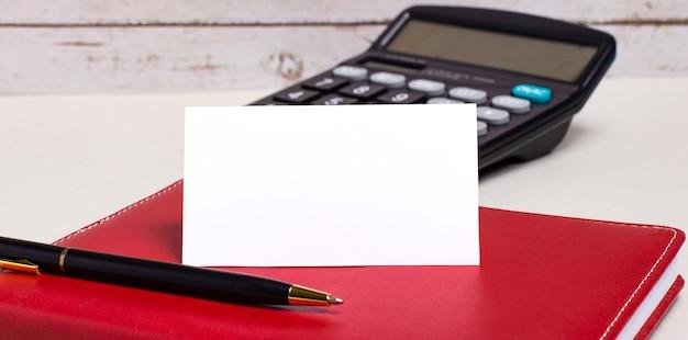 Auf dem bürotisch liegen ein weinrotes notizbuch, ein taschenrechner, ein stift und eine weiße leere karte mit platz zum einfügen von text. geschäftskonzept.