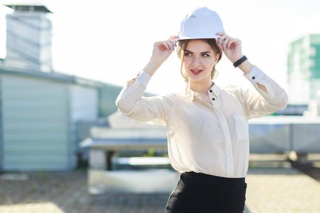 Auf dem dach steht eine schöne geschäftsfrau in weißer bluse, uhr, helm und schwarzem rock