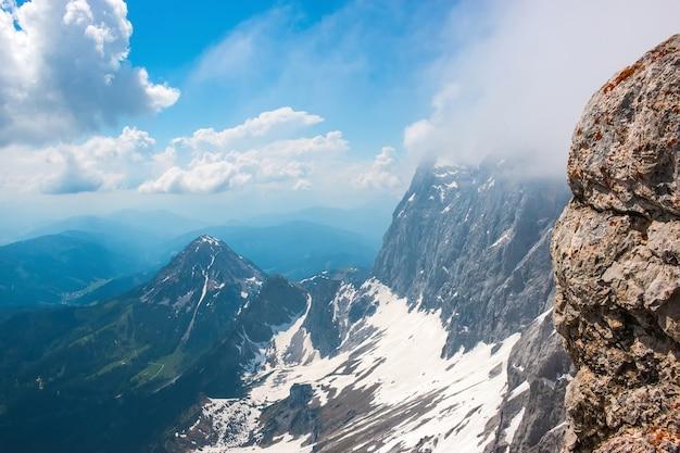 Auf dem dachsteingipfel und blick auf die alpen. nationalpark in österreich, europa. blauer und bewölkter himmel am sommertag