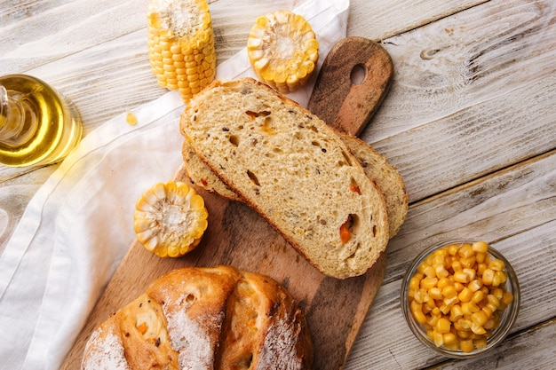 Auf dem dekorierten tisch frisch gebackenen mais und kürbisbrot in scheiben schneiden