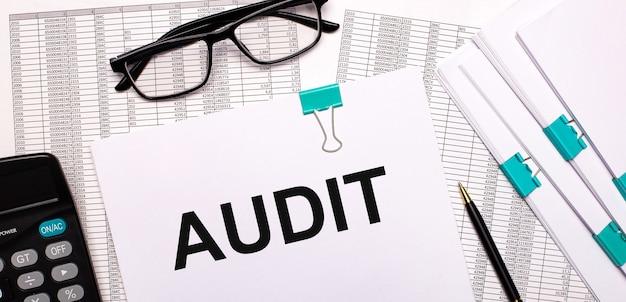 Auf dem desktop befinden sich berichte, dokumente, brille, taschenrechner, stift und papier mit dem text audit. geschäftskonzept