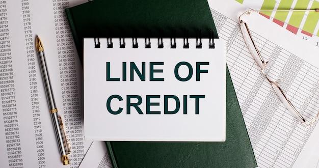 Auf dem desktop befinden sich berichte, eine brille, ein stift, ein grünes tagebuch und ein weißes notizbuch mit den worten line of credit. arbeitsplatznahaufnahme. unternehmenskonzept