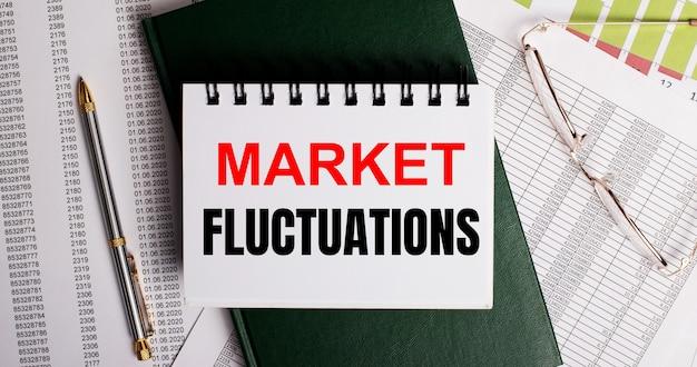 Auf dem desktop befinden sich berichte, eine brille, ein stift, ein grünes tagebuch und ein weißes notizbuch mit den worten market fluctuations