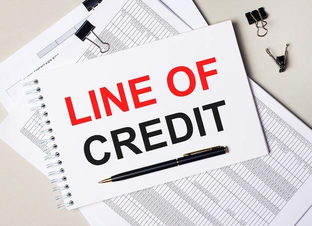 Auf dem desktop befinden sich dokumente, stift, schwarze büroklammern und ein notizbuch mit dem text line of credit. geschäftskonzept