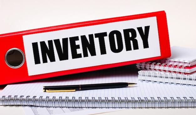 Auf dem desktop befinden sich notizbücher, ein stift und ein roter ordner für papiere mit dem text inventory. geschäftskonzept