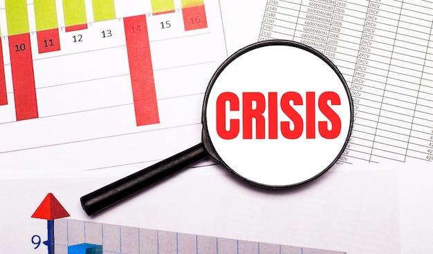 Auf dem desktop grafiken, berichte, eine lupe mit der aufschrift crisis.