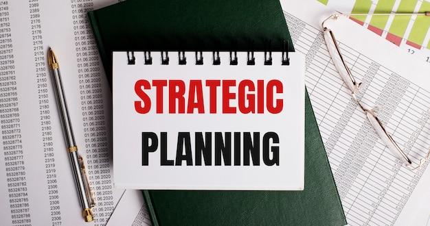 Auf dem desktop liegen berichte, eine brille, ein stift, ein grünes tagebuch und ein weißes notizbuch mit den worten strategische planung. arbeitsplatz nahaufnahme. geschäftskonzept